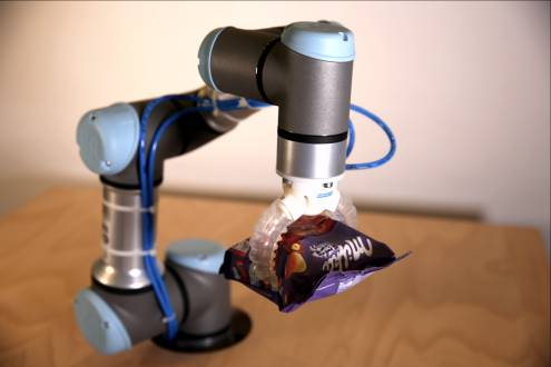 Soft gripper robot holding Milka chocolate bars